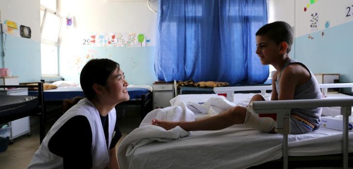 Sunyoung Park (instrumentadora quirúrgica) haciéndole compañía a un chico sirio en tratamiento en el hospital de Ramtha.