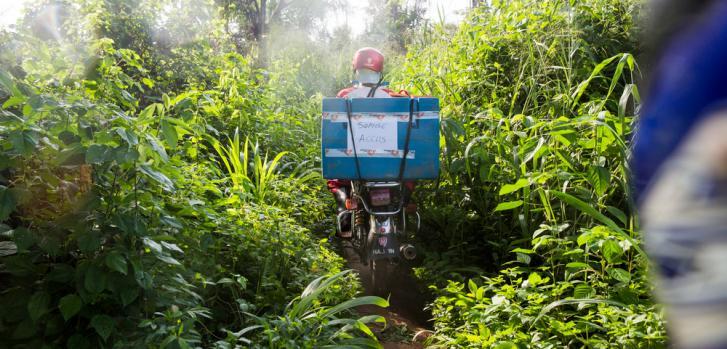 En moto, uno de nuestros trabajadores lleva bolsas de hielo hacia nuestros centros de vacunación, que sirven para mantener la cadena de frío. República Democrática del Congo, junio de 2016