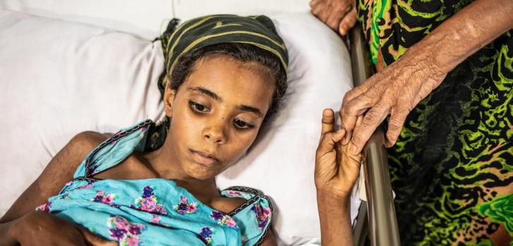 Amarah, herida por una mina cuando jugaba. Su abuela le sostiene la mano.