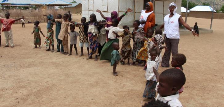 Niños y niñas en Pulka (Nigeria), realizando actividades recreativas con trabajadoras de Médicos Sin Fronteras.