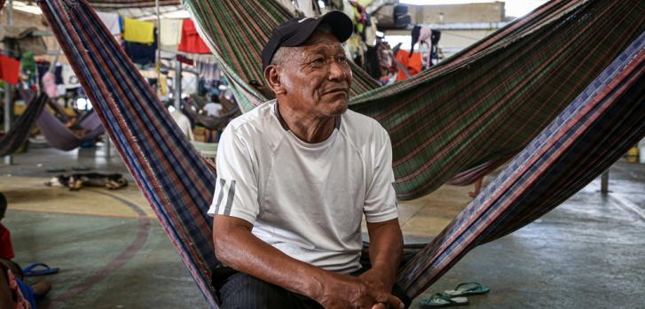 Delio silva es un hombre indígena del grupo étnico Warao. Está sentado en el área donde las personas duermen en hamacas, en un refugio ubicado en el barrio Pintolandia, Boa vista, en Brasil.