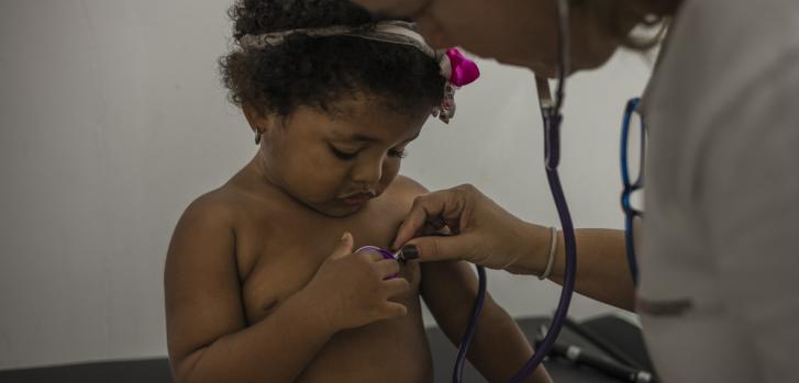 Fotografía tomada en octubre de 2019. Magali Gutieres, Directora de Actividades Médicas de MSF, está examinando a una niña durante una consulta en el ambulatorio de Anzoátegui.