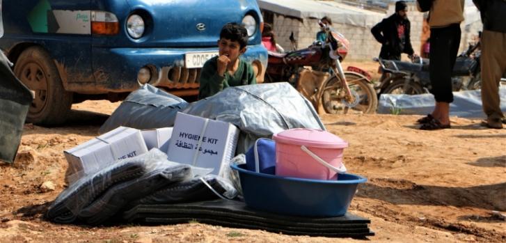 Un niño junto a kits de higiene distribuidos por Médicos Sin Fronteras en el área de Al habeet, noroeste de Siria.