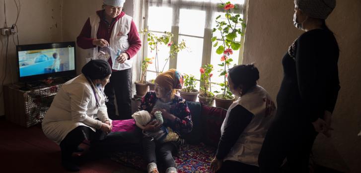Una madre y su hijo recién nacido reciben una consulta postnatal en su hogar, brindada por nuestros equipos junto al personal local del Ministerio de Salud en Syrt, Kirguistán.