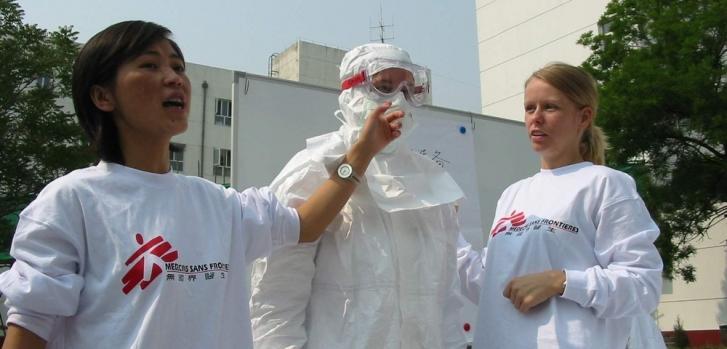 Mayo de 2003. Un equipo de MSF imparte un taller a trabajadores de salud locales sobre cómo vestir el equipo de protección en salas de aislamiento durante el brote de SRAS. Zhang Jia Kou, provincia de Hebei, China.