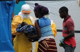 Foto: Deddeh, sobreviviente de Ébola, decide permanecer en el centro de tratamiento para cuidar al pequeño Elijah, cuya madre falleció a causa del Ébola. Foya, Liberia. ©Martin Zinggl/MSF