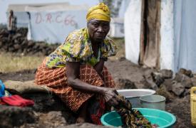 Jaqueline, de 73 años, lava su ropa dentro del campo para personas desplazadas de Bulengo en el que vive, en Kivu Norte. República Democrática del Congo, julio de 2014