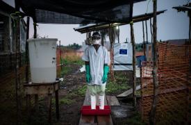 Higienista descontaminando sus botas en el centro de tratamiento de Èbola de Boende.