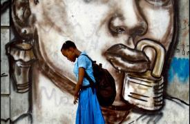 Una alumna de una escuela femenina en Puerto Príncipe pasa junto a un mural que representa la represión de las mujeres en Haití. (Grafiti de Jerry Rosembert) ©Patrick Farrell