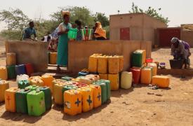 Personas desplazadas recogen agua limpia en un punto de agua en el distrito de Gorom Gorom, en la región desértica del Sahel, al norte de Burkina Faso. Febrero de 2021