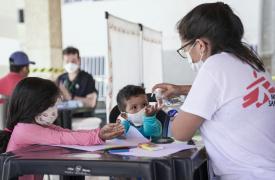 Una mujer de MSF le coloca alcohol en gel en las manos a un niño y una niña durante una clínica móvil en Fortaleza, Brasil, donde llevamos a cabo actividades de promoción de la salud y de salud mental. Junio de 2021