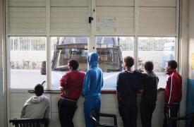 Un grupo de jóvenes provenientes de Eritrea miran desde la puerta del Centro de Recepción en Pozzallo, bloqueada con una camioneta para evitar que las personas escapen. ©Alessandro Penso