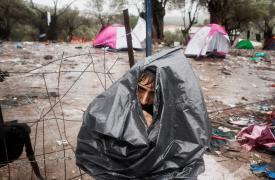 Octubre de 2015. un refugiado afgano se refugia de una tormenta con una bolsa de basura en el punto de acceso de Moria, Grecia.