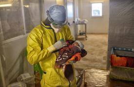 Trabajador sanitario de MSF alza en sus brazos a Nubia en el centro de tratamiento de Ébola de MSF en Conakry