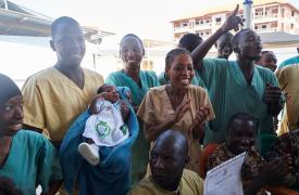 Ibrahima, el primer sobreviviente de ébola en Guinea sostiene en brazos a Nubia, la última paciente de la epidemia y la primera recién nacida que logra curarse. Sam Phelps