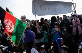 """""""Por favor abran la frontera"""" dice el cartel que sostienen refugiados afganos varados en la frontera entre Grecia y Macedonia, cerrada para ellos"""