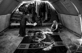 Dos niñas iraquíes limpian la alfombra de la carpa en la que viven con su familia en el campo de Bardarash, en el kurdistán iraquí  ©Manu Brabo/MEMO