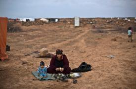 Un bebé sentado mientras su abuela pela berenjenas. Son refugiados sirios atrapados en el desierto, en la frontera con Jordania.