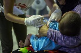 Un niño siendo vacunado por un integrante de MSF en Grecia. ©Pierre-Yves Bernard/MSF