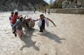 Adrien, Alejandro Hinojosa (especialista en agua y saneamiento de MSF) y Cassandre Saint-Hubert (enfermera de MSF) llevan equipamiento médico para hacer una clínica móvil del otro lado del río cerca de Seche, Port-a-Piment, Haiti. ©Joffrey Monnier/MSF