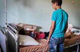Abdul Hadi tiene 9 años. Está en cama en la guardia de un hospital, acompañado por su hermano mayor, después de haber sido herido por una bomba barril mientras jugaba afuera de su casa en el área sitiada de Alepo.