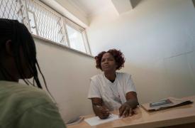 Olivia Mangwiro, psicóloga clínica, habla con una paciente en el ala de salud mental de la prisión de Chirubi. ©Rachel Corner/De Beeldunie
