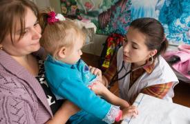 Ekaterina Pavlovna de 32 years años y su hija de 2, Tanya, durante una consulta médica con la Dra. Olga Taushan. La clínica móvil de MSF en Stepanivka se lleva adentante en un jardín de infantes, que también es usado parcialmente como un centro de salud.