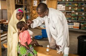 Fotografía que muestra a un miembro de nuestro equipo, proporcionando atención médica a una madre y su hija, en el campo de Ngala, Nigeria.