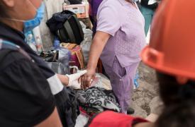 Ernestina Fuenleal (62 años, de violeta en la foto) junto a vecinos y rescatistas al frente de su casa que ha quedado inhabitable tras ser seriamente afectada por el terremoto en México. ©Jordi Ruiz Cirera