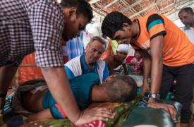El Dr. Ian Cross habla con un paciente, que tiene el fémur fracturado tras un ataque de un elefante, en la clínica de MSF en Kutupalong, Bangladesh. ©Paula Bronstein/Getty Images