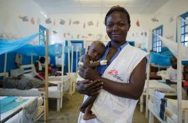 Patiente Ngangu, enfermera de Médicos Sin Fronteras (MSF) junto a Yapele, un paciente hospitalizado en la Unidad Terapéutica de Nutrición Intensiva del Hospital Bili, que cuenta con el apoyo de MSF en República Democrática del Congo.