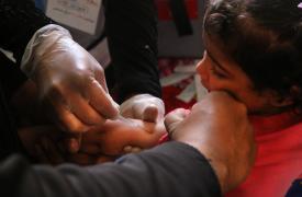 Una enfermera vacuna a una niña siria contra neumonía y sarampión en Atarib, Syria.