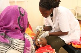 Una enfermera prepara a un niño con desnutrición severa para recibir una transfusión.