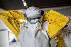 Un trabajador sanitario se coloca su equipo de protección personal para ingresar al Centro de Tratamiento de Ébola en Bunia (República Democrática del Congo), apoyado por Médicos Sin Fronteras.