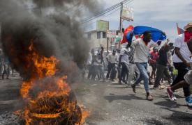 Varios manifestantes haitianos corren cerca de neumáticos en llamas durante una manifestación en Puerto Príncipe que pide la salida del presidente Jovenel Moïse, el 9 de junio de 2019.