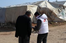 Un trabajador comunitario de Médicos Sin Fronteras está hablando con un sirio desplazado en el campamento de Qadimoon, al noroeste de Siria, para alentarlo a vacunar a sus hijos.
