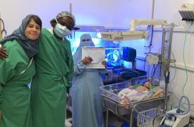 Parte del equipo de Médicos Sin Fronteras junto a un bebé recibiendo tratamiento con oxígeno en Yemen.