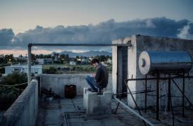 Un joven intentando acceder a la red telefónica en la terraza del Hotel abandonado Captain Elias, para avisarle a sus amigos que está bien © Alessandro Penso